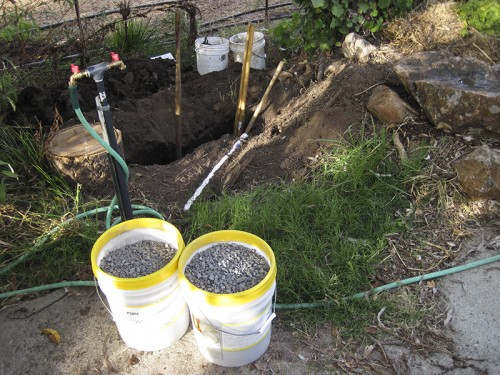 "gravel layer under landscape cloth and sedge plants will ""french drain"" the water into a rock-filled hole"